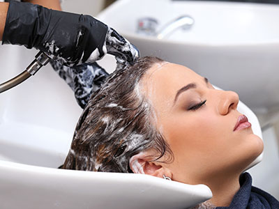 image of lady getting her hair shampooed