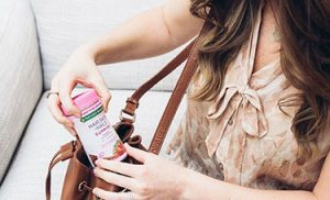 girl sitting on couch pulling vitamins out of purse