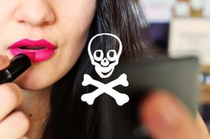 girl putting on lipstick with skull and cross bones in center