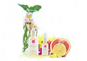skin care bottles with grapefruit and flowers in vase