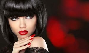Beauty Fashion model girl portrait. Brunette woman with red lips, red manicured nails and stylish bob hairstyle posing over dark red bokeh background.