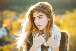 Woman with long hair and natural makeup. Fashion model with pretty face. Girl on autumn natural background. Beauty and fashion. Season and fall holiday.