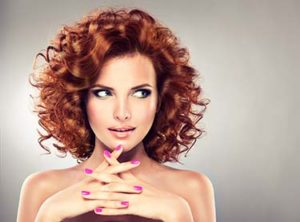 Beautiful model with red curly hair and pink manicure nail . Redhead girl with smile